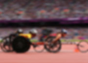 three women in wheelchair bycicles on track, with helmets,. public on the background.