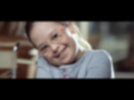 still of the video - girl with Down syndrome smiling.