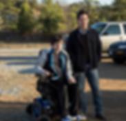 Cena externa, em um estacionamento, rapaz em cadeira de rodas ao lado de homem em pé, ao seu lado.