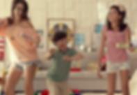 Menino com sindrome de Down em uma sala, danca entre duas adolescentes sem a sindrome.