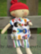 ragged doll with amputed arm and colorful outfit and red hat.