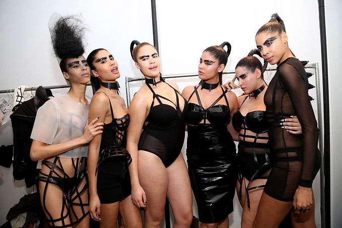 Six women of all sizer and ethnicities wearing black bikinis, dresses and maillots, in the dress room. They all have black painted eyebrows and poneytails.