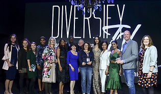 group of 15 people, women, man, different ethnicities, on a stage, carrying awards, Diversify tv written on the background.
