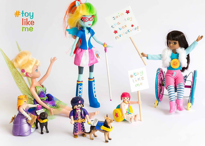 "On a white background, various toys with disabilities, tinkerbell with a cochlear implant, a princess with a guide dog, a sheik with a guide dog, a minifigure in a wheelchair and a sign that reads #ToyLikeMe, a rainbow coloured doll with glasses and a cane and a Barbie like brunette doll in a wheelchair with a sign that reads ""join the toy box revolution!"""
