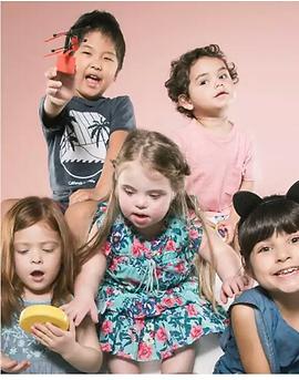 cinco crianças brincando, entre elas uma menina com sindrome de down.