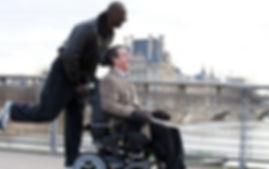 Homem em cadeira de rodas sendo empurrado por outro homem, em uma ponte sobre um rio com um predio antigo ao funco. Os dois esão rindo.