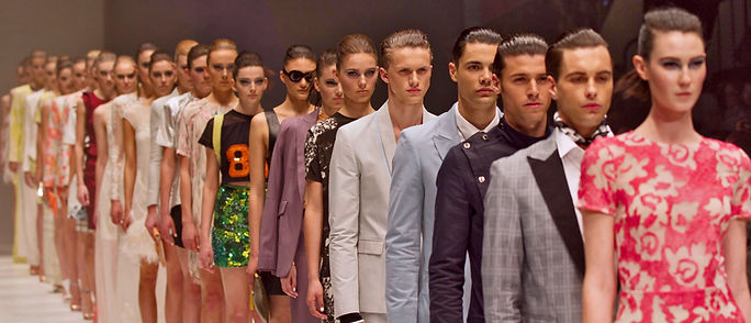 A group of models in line on the runaway, all tall, slim and white man and women, with different clother, the same hairdo, combed back.