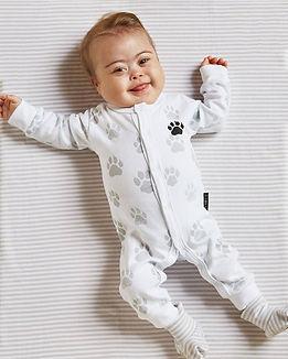 Bebê sorrindo, deitado na cama, com macacão com patinhas de felino cinza.