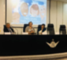 mesa de evento. 2 mulheres e um homem - na tela, capa do guia tres vivas para a adocao.