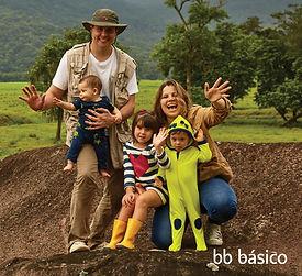 familia em cima de uma pedra, no campo. pai, homem com chapeu, com bebe no colo, apoiado no joelho, menina e menino com sindrome de down em frente a mulher, todos sorriem e dao tchau.