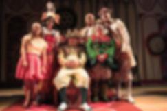 6 atores fantasiados, um com roupa de rei sentado num trono.