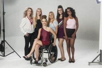 6 mulheres, 5 de pe e uma em cadeira de rodas, num setting fotografico.