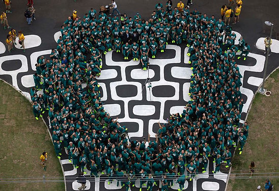 Foto vista de cima, dos 286 atletas paralímpicos brasileiros reunidos formando um coração, sob a calçada de pedras portuguesas do Boulevard Olímpico, quando de sua apresentação à cidade para as Paralimpíadas. Eles vestem todos o uniforme verde da delegação brasileira.
