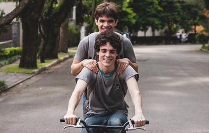 dois rapazes sorridentes andam na rua de bicicleta, um deles de pé néa garupa do outro.