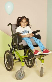 Menina em cadeira de rodas, de maria xiquinha, sorrindo, veste blusa rosada, legging azul e tênis vermelho.