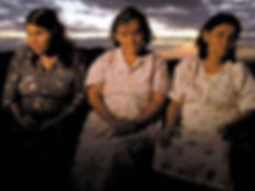 3 mulheres cegas, uma sentada ao lado da outra, e o por do sol por tras.