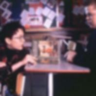 Dois garotos sentados a mesa em uma escola, um deles mostra um livro para o outro.