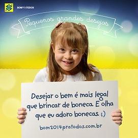 Menina com sindrome de Down segura placa dizendo - desejar o bem é mais legal que brincar de boneca. E olha que eu adoro bonecas ;) bom2014pratodos.com.br.