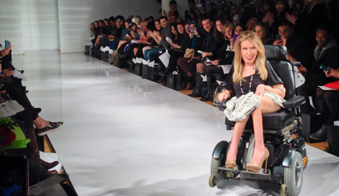 Model Danielle Sheypuk, on the catwalk in her wheelchair. People wactching the show on the sides.