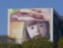foto de outdoor em prédo - menina com síndome de down, duas mãos, uma branca e uma negra se entrelaçando. Texto. Semna da Pátrica. Igualdade e Inclusão. A educação éo caminho.