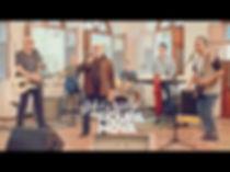 grupo roupa nova, com 2 guitarras, baixo, bateria, teclado e vocal, cantando numa casa.