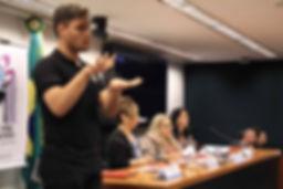Mesa dos debatedores em segundo plano, intérprete de libras em primeiro plano.