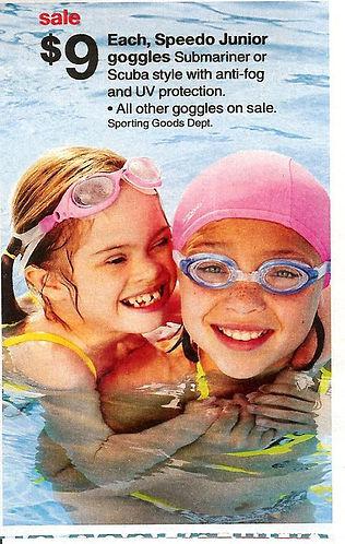 duas meninas com oculos de nadadoras, uma delas com touca, brincam na piscina,