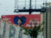 vista de outdoor da campanha, com muro e arvore na frente, predio atras. menino com sindrome de down debrucado em janela de coracao - dia das maes.