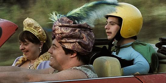 Dois homens e uma mulher sorrindo e fantasiados em um carro, um dos homens dirige.
