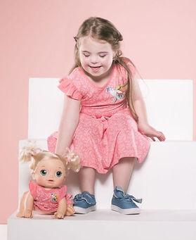 menina comvestido roado, brinca com boneca com o vestido igual.