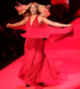 Actress and transgender advocate Lavender Cox in a red dress with a cape, walking the catwalk, with her long blond hair floating.