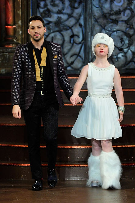 Madeleine with white dress, fur white hat and boots, hand in hand with male model with black suit outfit, with a yellow bow tie, untied, walking the catwalk.