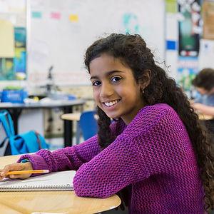 Jeune fille assise à un pupitre un jour de classe.