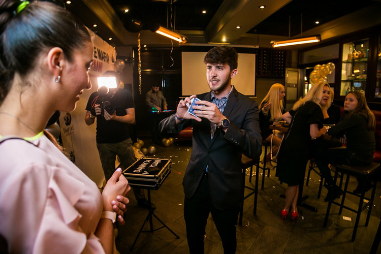 Danny performing a card trick for a guest at a company launch party!