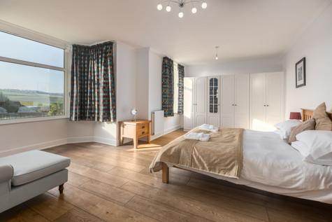 This vast bedroom invites long lie ins, enjoying the sea views
