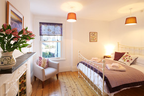 Wooden floors and an iron bedstead invoke tradition and charm in this bedroom
