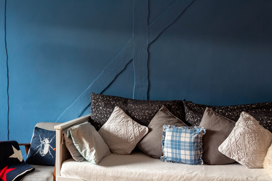 The sofa in Cottage 4, with wall colour inspired by the Cornish coast.