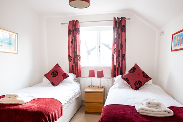 A bright twin room with red decor