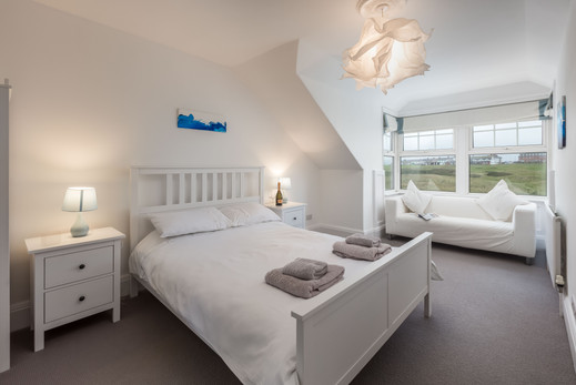 A double bedroom with comfy sofa