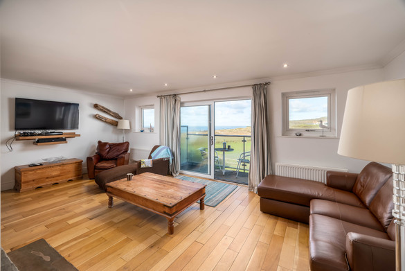The living room has a welcoming wooden floor and flatscreen television for nights in