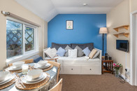 Cottage 2's living and dining area, with the table laid ready for a tasty Cornish breakfast.