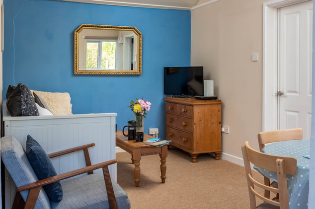 Cottage 3's living area with sofa, easy chair and dining table.