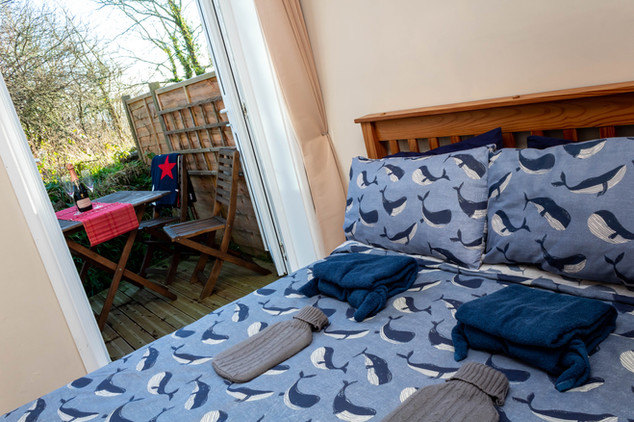 Relax in Cottage 3's double bedroom with cosy hot water bottles.