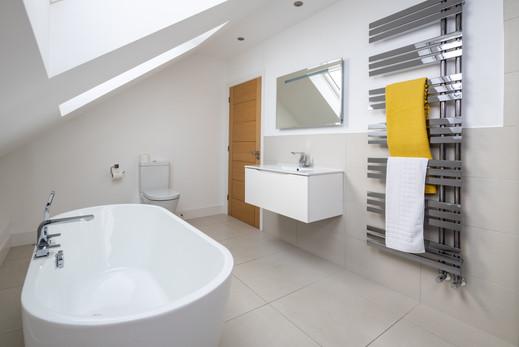 Large bathroom with freestanding bath and heated towel rail
