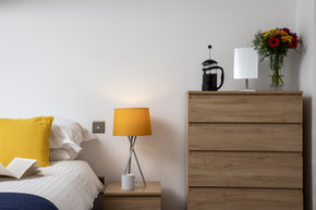 Bedside with coffee cup, cafétiere and fresh flowers