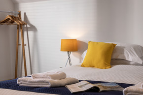 Bed with bedside lamp and hanging space