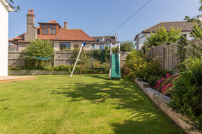 The lush green lawn, complete with slide, is a child's delight