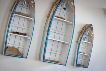 Handmade miniature boats hang on the wall