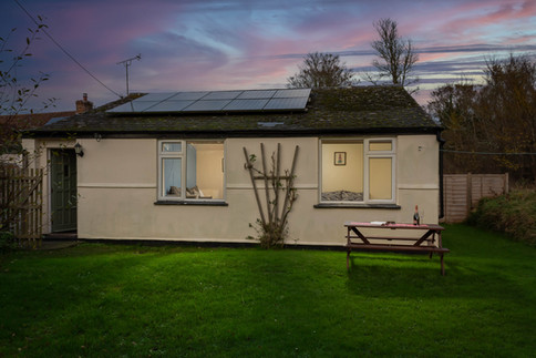 A Cornish sunset lights up the sky behind Cottage 4 at Little Gwendreath.