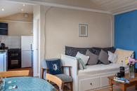 Enjoy a coffee while relaxing on the sofa in Cottage 3's living area.